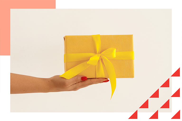 female hand holding small yellow gift box with a bow