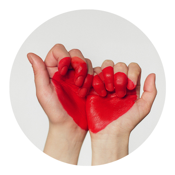two hands forming a heart with red paint